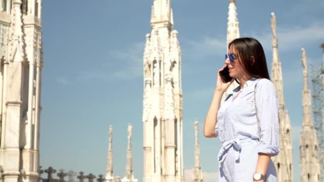 vídeos de stock e filmes b-roll de women talking on the phone at the milan cathedral - religião