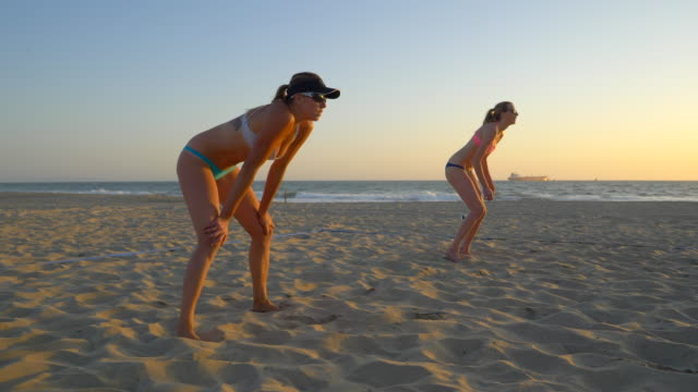 women teams play beach volleyball at sunset and a player passes the ball. - slow motion - sonnenschild stock-videos und b-roll-filmmaterial