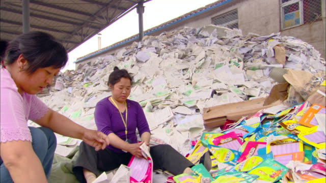 ms zo women tearing up paper pamphlets at recycling plant, beijing, beijing, china - リサイクル工場点の映像素材/bロール