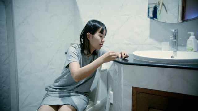 women testing on pregnancy test kit in bathroom - testing kit stock videos & royalty-free footage