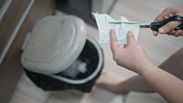 vídeos de stock e filmes b-roll de women throwing the protective face mask into the trash bin,slow motion - lixeira
