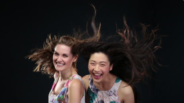 ms slo mo women throwing their heads back, hair moving in wind / london, greater london, united kingdom - greater london video stock e b–roll