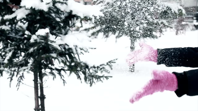 women throws snow,hands  with pink gloves, close up