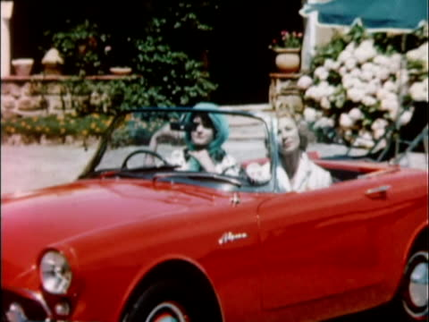 1959 WS ZO Women tie scarves over their heads while sitting in red 1959 Sunbeam Alpine convertible / USA
