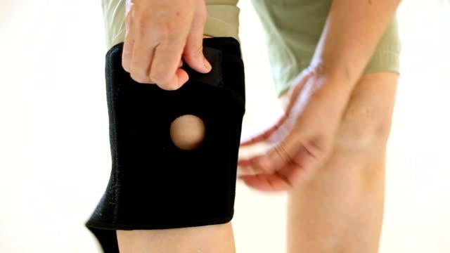 vídeos de stock, filmes e b-roll de mulheres de lesões de joelho e usar o joelho suportam cinta na perna - brace