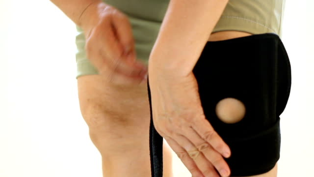 women to knee injury and use support brace on leg - leg brace stock videos and b-roll footage