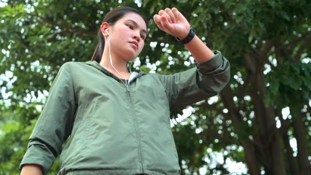 stockvideo's en b-roll-footage met vrouwen raken aan om een smartwatch te controleren en op te zetten voordat ze gaan sporten. - jogster