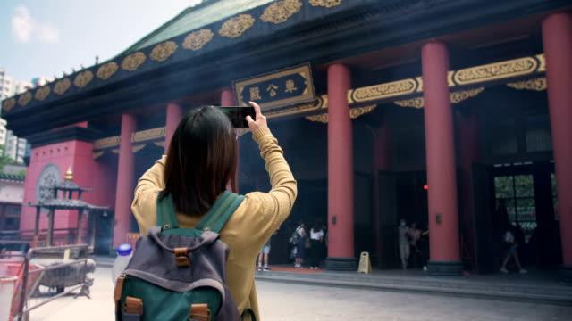 Frauen-Touristen nehmen Sie ein Foto im alten Tempel in Hong Kong