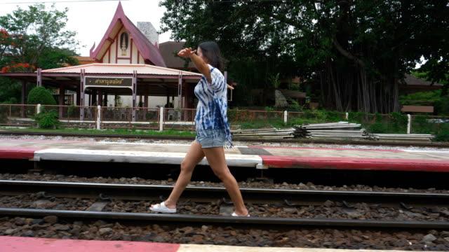 stockvideo's en b-roll-footage met vrouwen toeristische lopen op de spoorlijn in het treinstation van hua hin - vrouwelijke gestalte