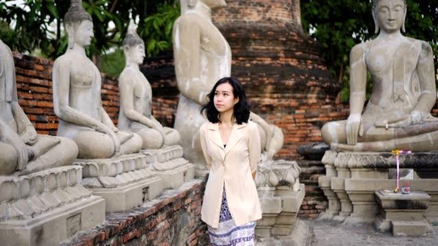 vídeos de stock, filmes e b-roll de turistas de mulheres no templo da tailândia - escultura