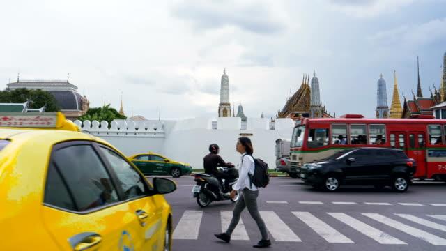 stockvideo's en b-roll-footage met vrouwen reiziger kruising de weg naast grand palace in bangkok - menselijke rug