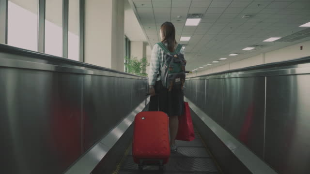 women traveler on moving walkway in airport - wheeled luggage stock videos and b-roll footage