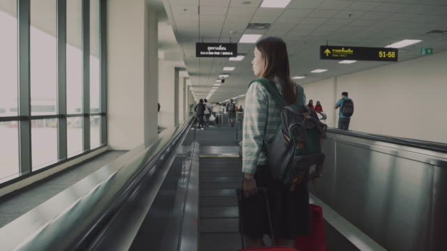Women Traveler On Moving Walkway In Airport