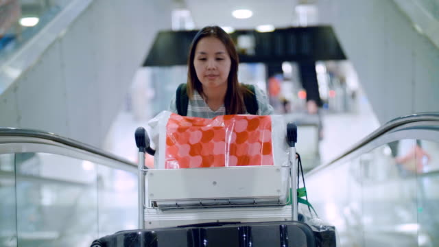 women traveler on moving walkway in airport - only mid adult women stock videos and b-roll footage