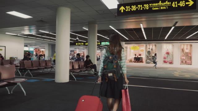 frauen-reisenden mit roten gepäck im flughafen-terminal zu fuß - städtereise stock-videos und b-roll-filmmaterial