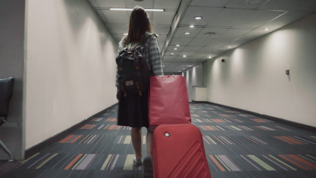 women traveler with red luggage walking through airport terminal - bagaglio video stock e b–roll
