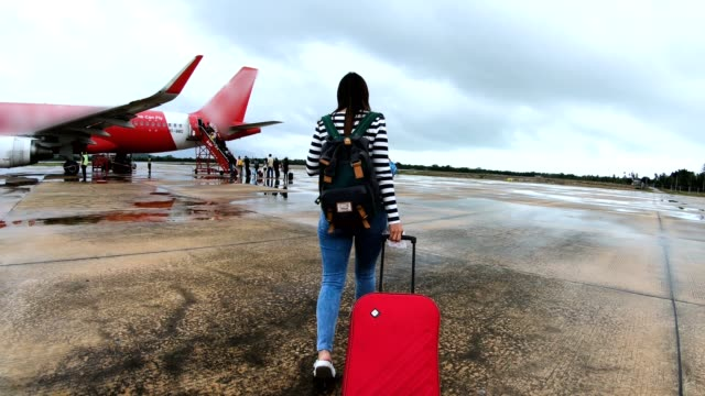 women traveler with red luggage walking to airplane - wheeled luggage stock videos and b-roll footage