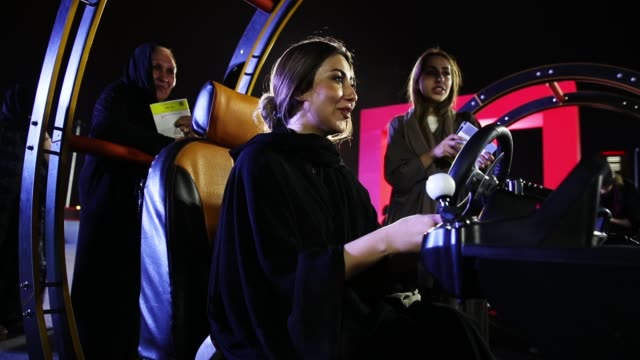 women trie out a car driving simulator during an outdoor educational driving event for women on june 21, 2018 in jeddah, saudi arabia. saudi arabia... - jiddah bildbanksvideor och videomaterial från bakom kulisserna