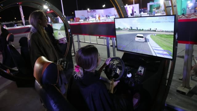 vídeos de stock, filmes e b-roll de women try out a car driving simulator during an outdoor educational driving event for women as other women look on on june 21 2018 in jeddah saudi... - vestimenta religiosa