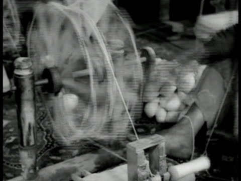 women turning spinning wheel putting wool onto spindles ws three girls working on hanging rug strings profile of child weaving rug hand knotting... - 1951 stock videos & royalty-free footage