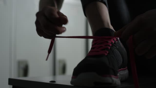 women tying her shoelaces in locker room - locker room stock videos and b-roll footage
