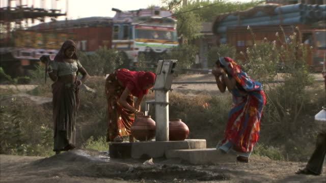 women use a water pump beside a busy road. - water pump stock videos & royalty-free footage