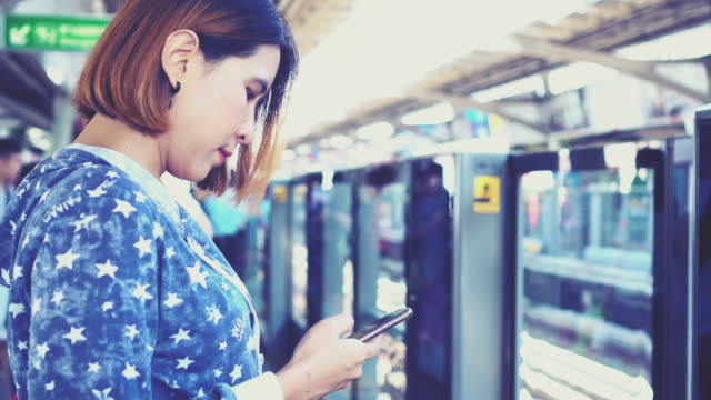 Women use smart phone waiting train