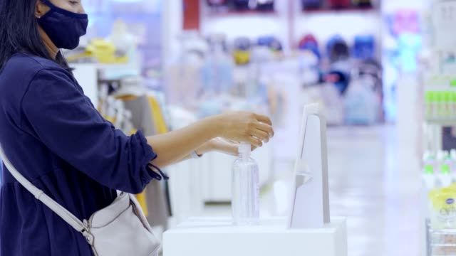 women uses hand sanitizer in shopping mall - rubbing alcohol stock videos & royalty-free footage