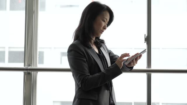 女性がスマートフォンを使用して、ウィンドウ - 事業戦略点の映像素材/bロール