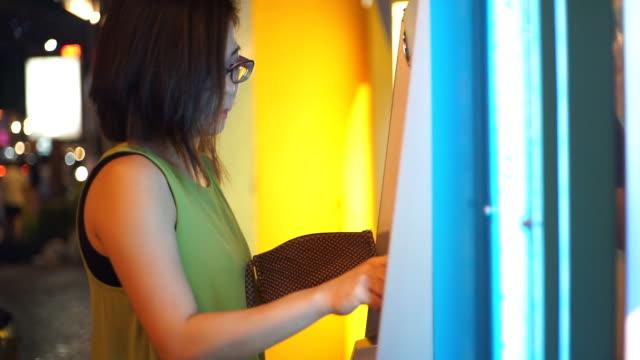 vídeos y material grabado en eventos de stock de mujeres que usan el cajero automático mientras mano introducir pin en el teclado de máquina de cajero automático banco. - cajero