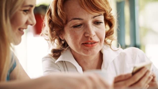 Frauen mit Handy im sonnigen café