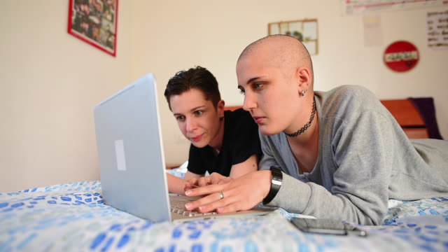 Women using laptop on bed