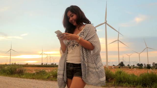 Frauen mit Handy in der Prak einer Windkraftanlage