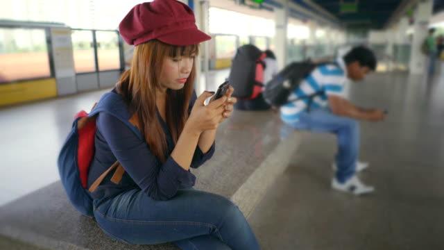 vídeos de stock, filmes e b-roll de mulher usando telefone celular em uma estação de trem - transporte público