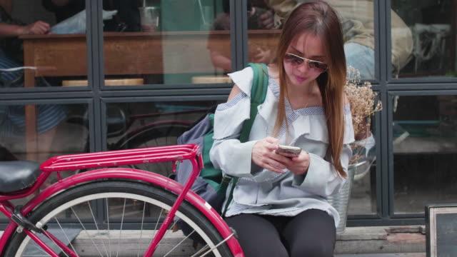 women using mobile phone while waiting for her boyfriend - solo una donna di età media video stock e b–roll