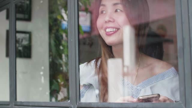 vídeos de stock e filmes b-roll de women using mobile phone while waiting for her boyfriend - só mulheres de idade mediana