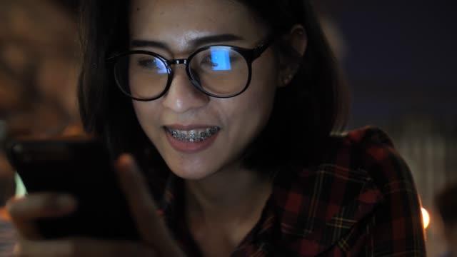 Women using Smart phone at night, Reflection on Eyeglasses
