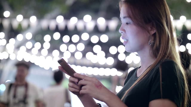 Women Using Smart Phone In a Party At Night