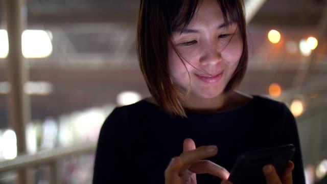 frauen mit smartphone in einem regen in der nacht in bangkok - abspann stock-videos und b-roll-filmmaterial
