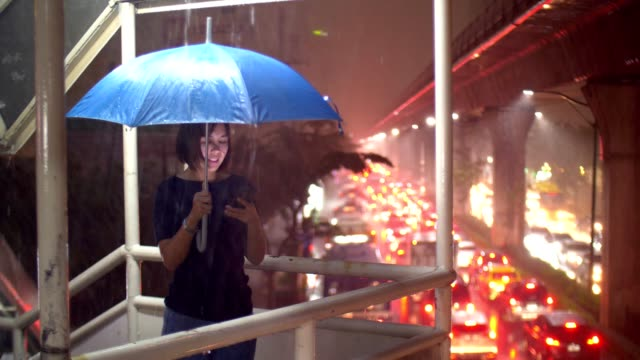 women using smart phone in a rain at night in bangkok - scrolling stock videos & royalty-free footage
