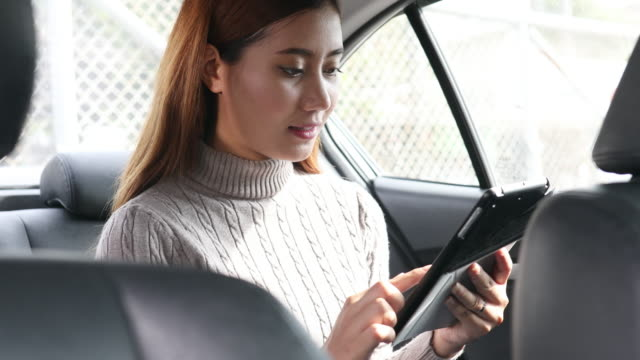 Women using smart phone on Passenger seat in the car