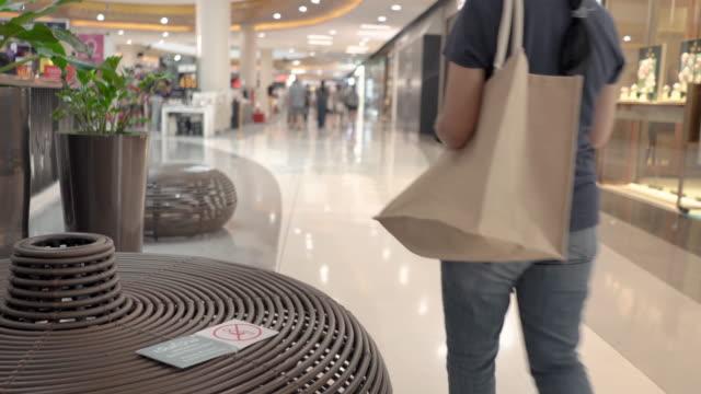 vídeos de stock, filmes e b-roll de mulheres usando telefone inteligente sentado no banco para o distanciamento social durante a pandemia de coronavírus covid-19 - shopping center