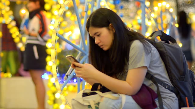 Women using smartphone in celebration event at night