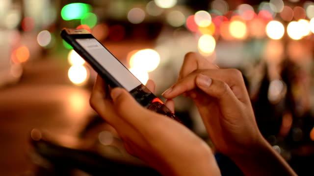 Women using smartphone, night.