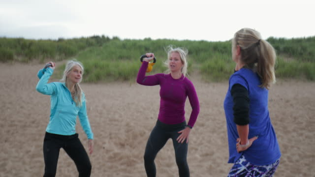 Women Using Weights on the Beach