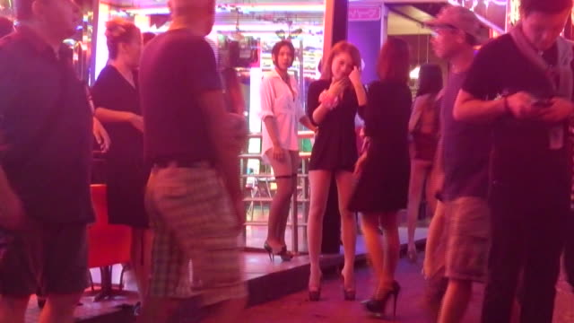 women wait for customers in front of a gogo bar on soi cowboy bangkok on the day the government relaxed mourning restrictions the king of thailand... - nutten stock-videos und b-roll-filmmaterial