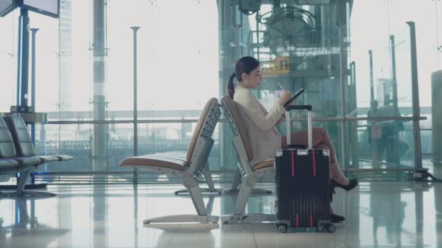 vidéos et rushes de les femmes en attente d'embarquement. - tenue d'affaires formelle