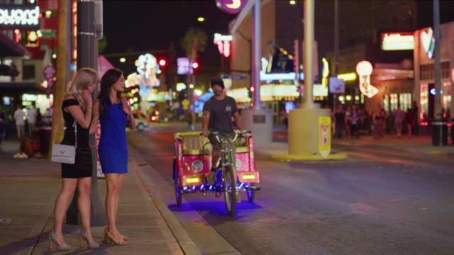 Women waiting on sidewalk then riding in pedicab in city at night / Las Vegas, Nevada, United States