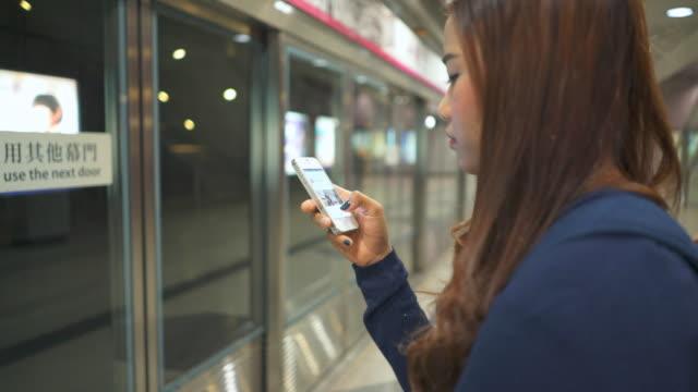 Women waiting The train and Using smart phone