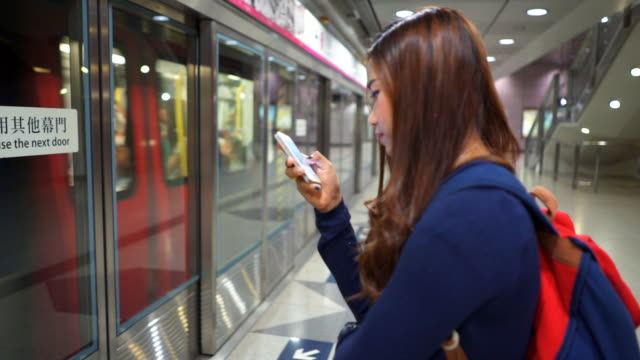 Women waiting The train and Using smart phone